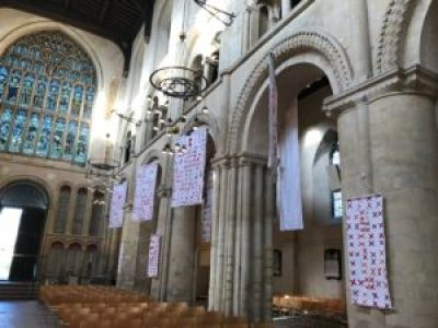 quilts made of pairs of red X's sewn to white background fabric hang in the cathedral