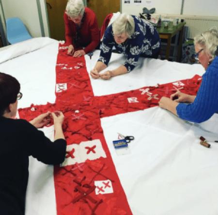 women stitching red X's onto white fabric