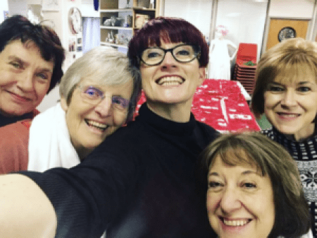 five smiling women who appeared in other photos as they were stitching the red X's to the expansive piece of white fabric