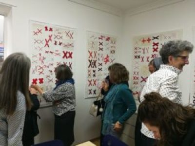 women admire quilts made of pairs of red X's on a white background