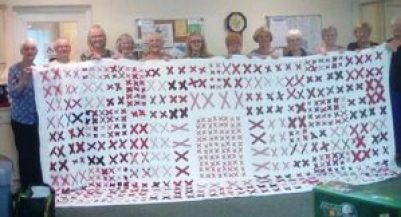 a group of women hold a large white quilt covered with pairs of red X's