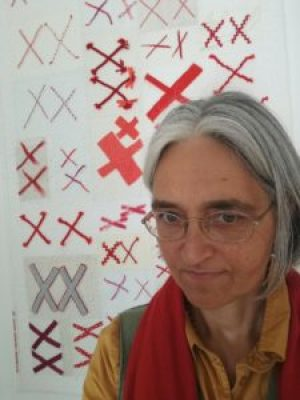 Woman standing in front of a quilt made of pairs of red X's on a white background