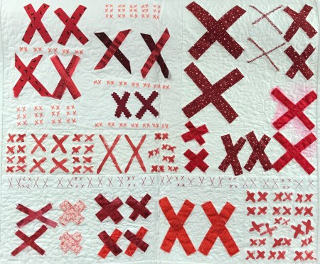 white quilt covered with multiple pairs of red X's