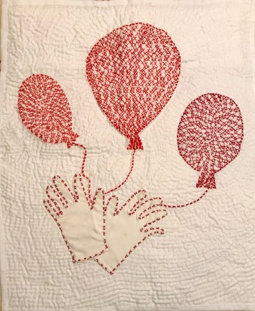 white quilt base decorated with balloons created using pairs of red X's and a child's pair of gloves holding onto the strings of the balloons