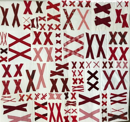 white quilt base covered with pairs of red X's