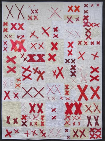 white quilt covered with pairs of red X's