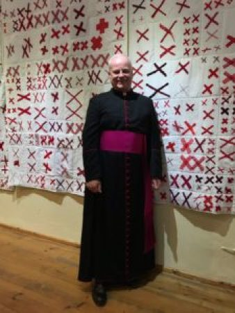 a reverend stands before white quilts adorned with pairs of red X's