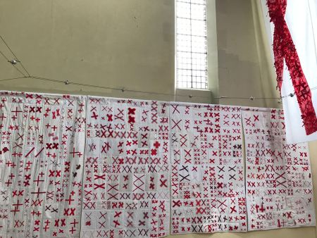 a wall covered with quilts with a white base, each filled with pairs of red X's