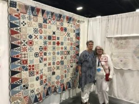 two women stand beside a multi-colored quilt