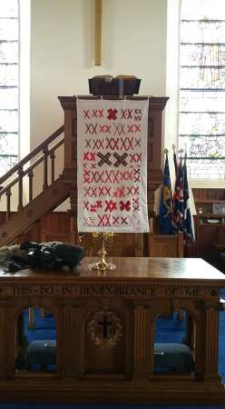 a white quilt covered with pairs of red X's hangs on a church podium surrounded by two windows