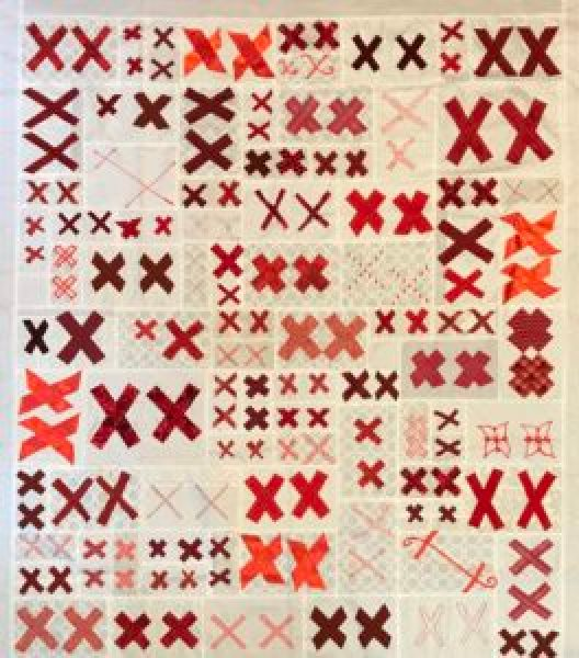 a white quilt covered with pairs of red X's
