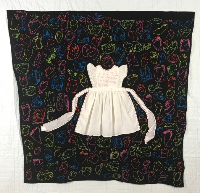 little girl's white dress with sash sewn over a black quilt filled with colorful stitched scribbles