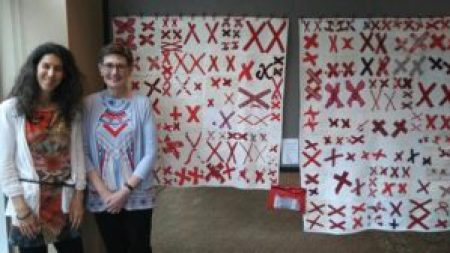 two women stand in front of two white quilts covered in pairs of red X's