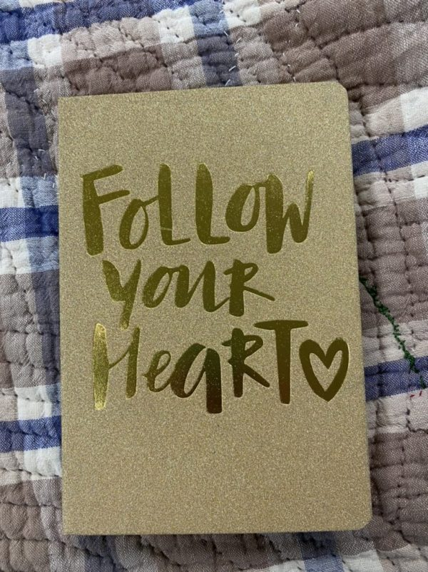 gold journal on old brown, white, and blue quilt. on cover of journal is Follow Your Heart.