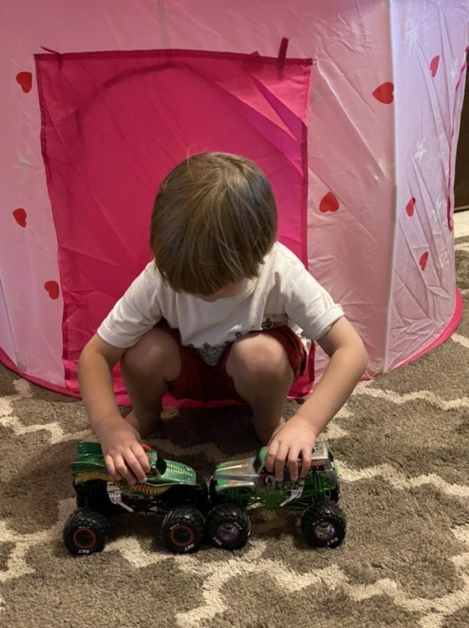 the young boy puts two toy trucks together