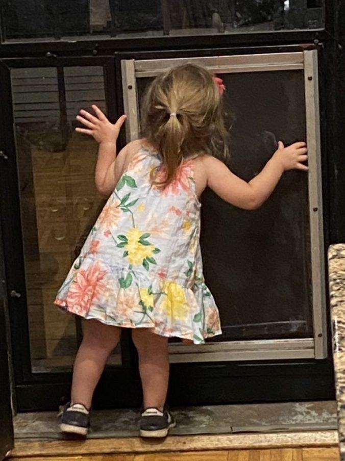 little girl looks through door