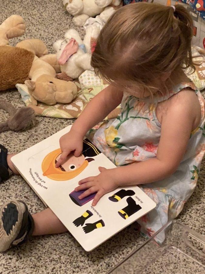 a little girl reads a book about firemen