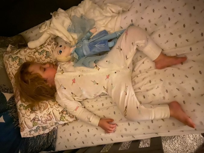 a young girl sleeps with Ana from Frozen