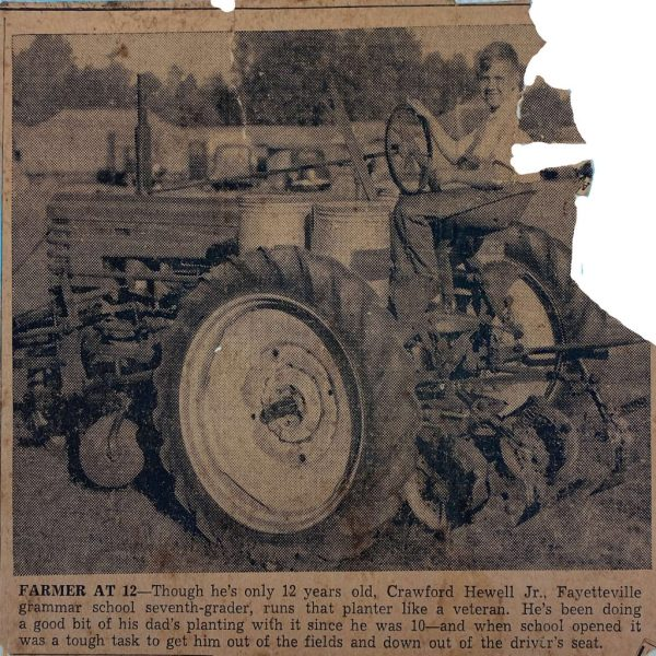 a young boy sits behind the wheel of a tractor