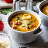 Tomato Tortellini Stew in white bowls with tomatoes on the vine, salt and pepper shakers, spoons and colander