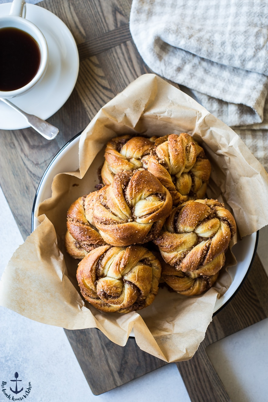 Overhead photo of Cinnamon Pecan Knots in dish with cup of coffee