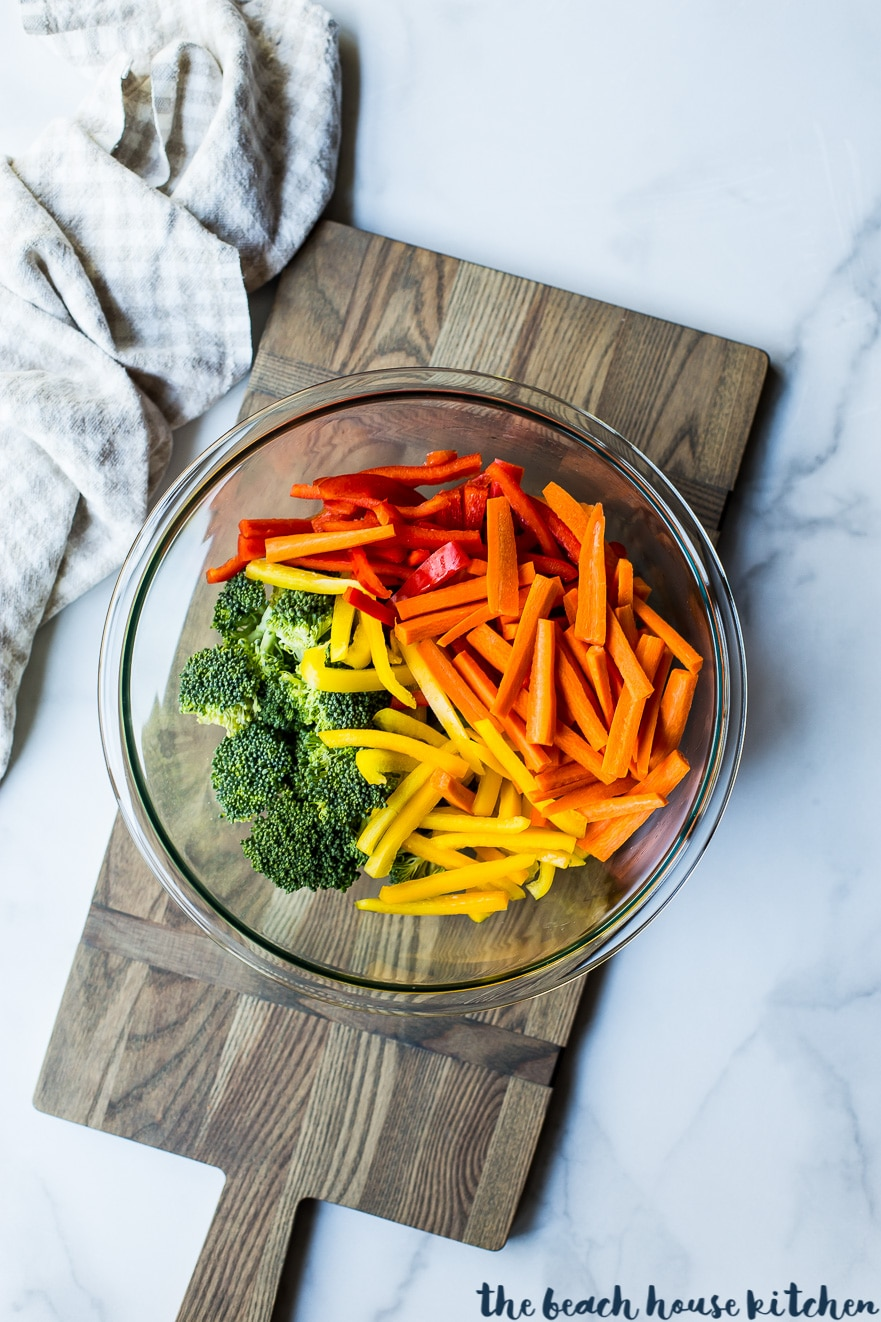 Overhead photo of broccoli, red and yellow peppers and carrots in a glass bowl on a wooden board