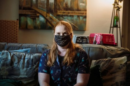 Casye Davidsons sits on a couch in her Hyde Park apartment.