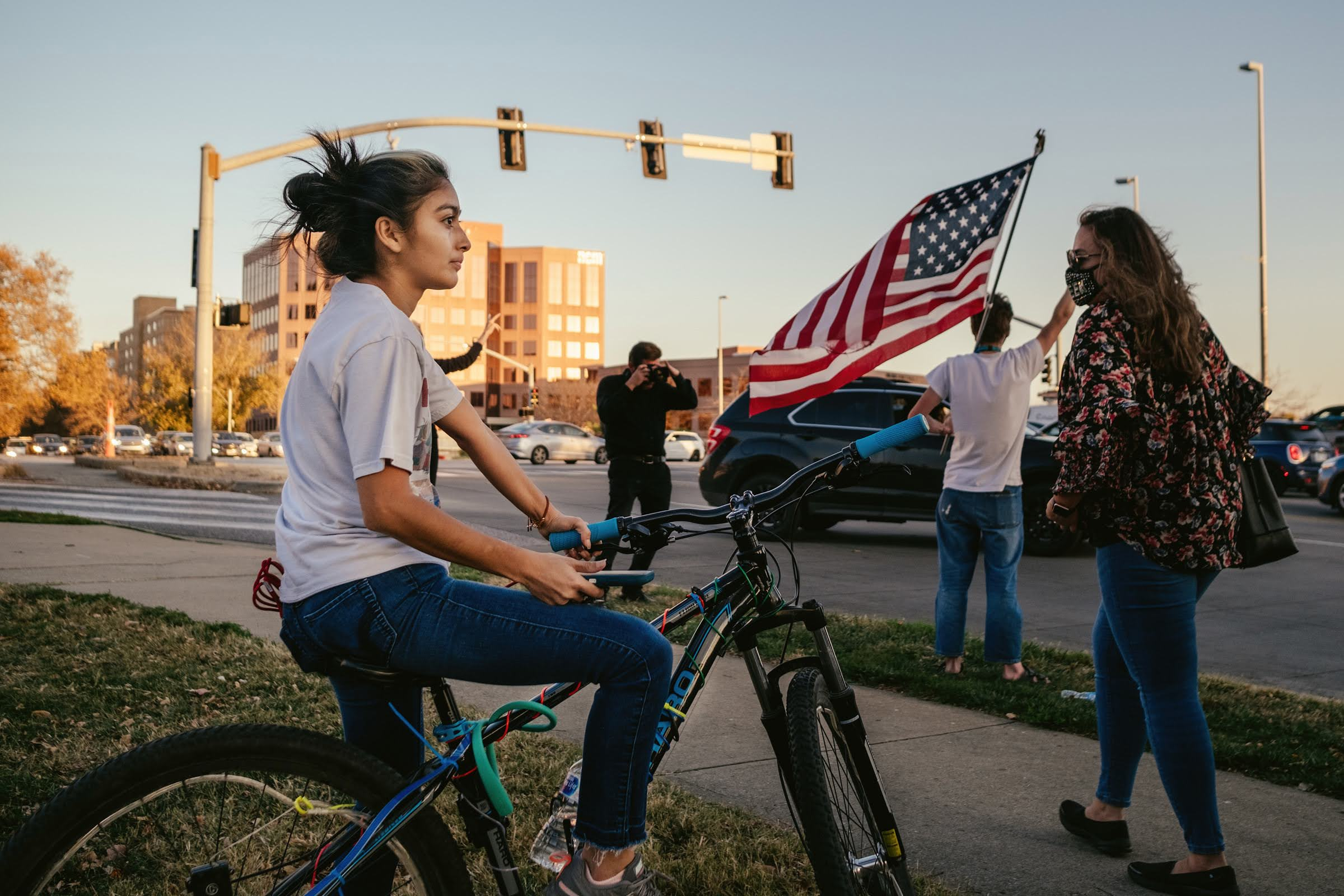 A celebration attendee looks on quietly from their bike as others wave flags, dance, and celebrate the Biden-Harris victory. Chase Castor/The Beacon