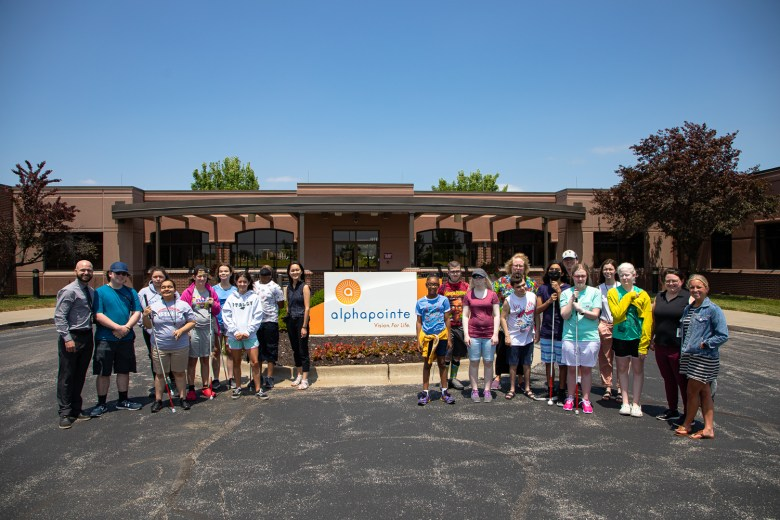 A group of about 20 campers and staff pose around the Alphapointe sign in front of the company's headquarters.