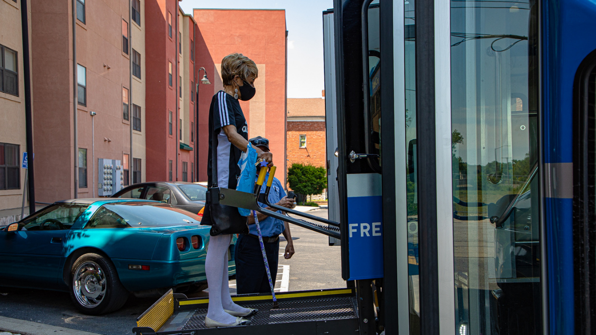 Toni Adams, a female RideKC Freedom user, boards the paratransit bus. The driver stands behiind her, helping her board.