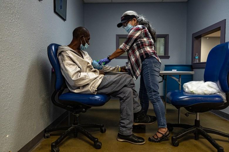 Volunteer nurse Regina Ancola checks the blood pressure of a patient at Street Medicine KC's weekend medical clinic.
