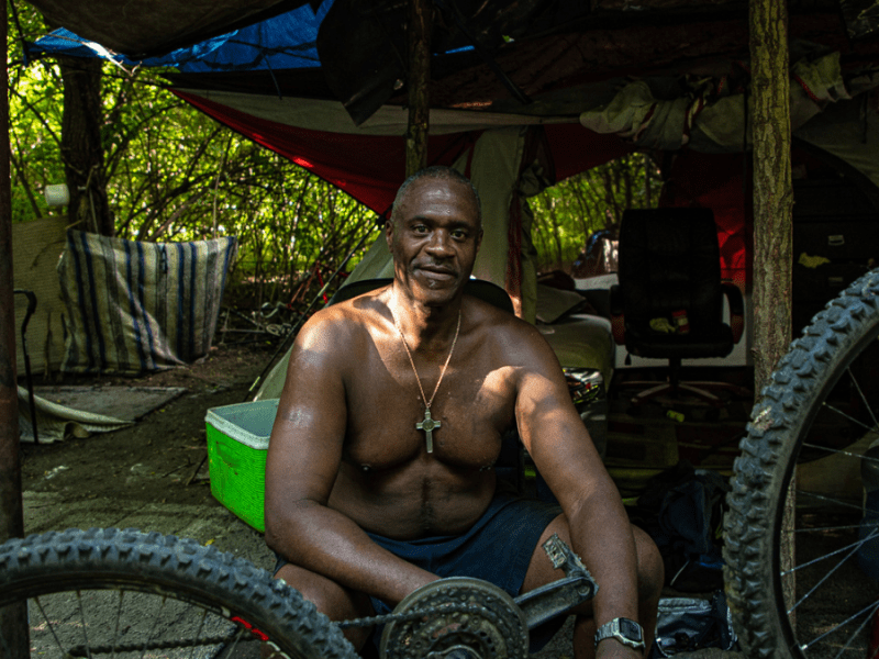 Michael Lee Perry, an unhoused man, works on his bike at his camp site in Kansas City.