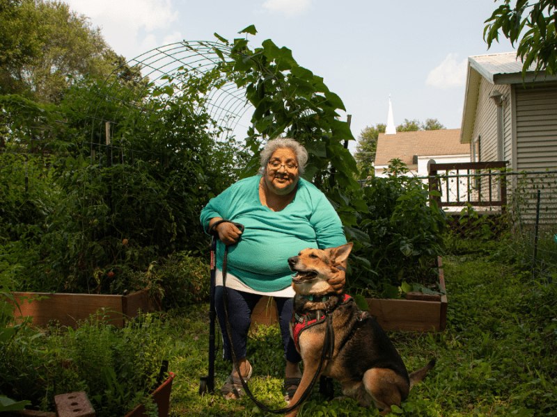 Louise Lynch and her dog sit in her garden in Kansas City, Kansas. She's faced the threat of a utility shutoff in recent months.