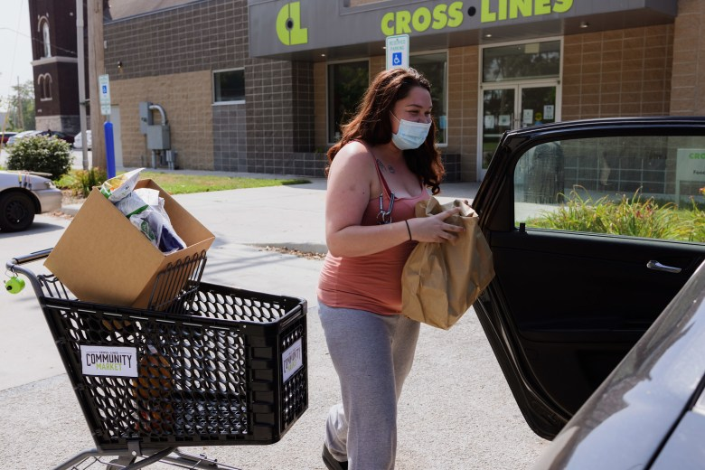 Brittany Patton loads groceries into her car after shopping at Cross-Lines Community Market in Kansas City, Kansas.