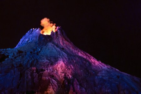 Mount Prometheus erupting at night, lit up in blue and pink at Disney Sea