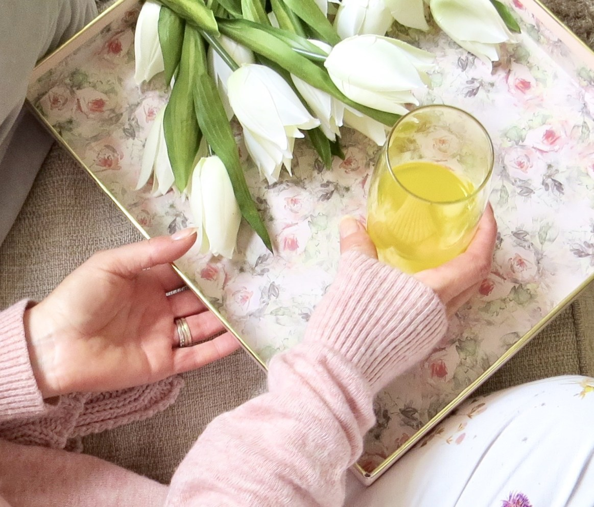 here I'm holding a floral tray with a glass of Skinade Collagen drink.