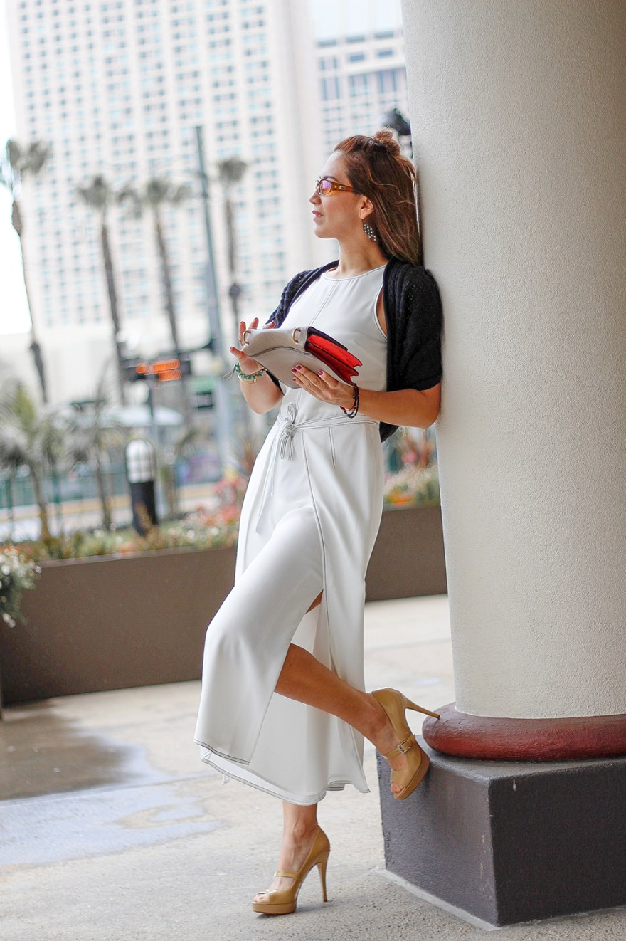 woman wearing a white jumpsuit  with a touch of black by wearing a cropped sweater