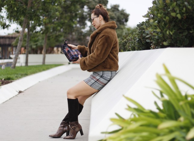 woman wearing a faux fur coat paired with a plaid dress