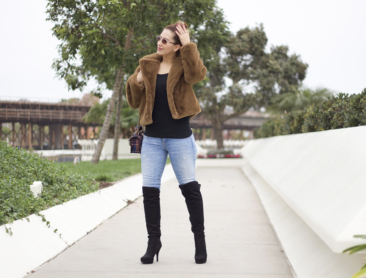 woman wearing a faux fur coat paired with jeans and over the knee boots. Her idea was to create cute winter outfits that look stylish.