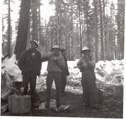 No time for tea as loggers eat lunch standing up and stir their coffee with their thumbs. L-R: Timber faller Ben Jasper, Jack Hopkins, Cat skinner Maurice Olson, and timber faller Sox Stevens.