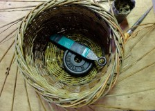 Some basket making tools: a weight holds the basket still as you work, a rapping iron for tapping down the weave, a bodkin for opening and holding a gap between rods, a tin of grease helps too.