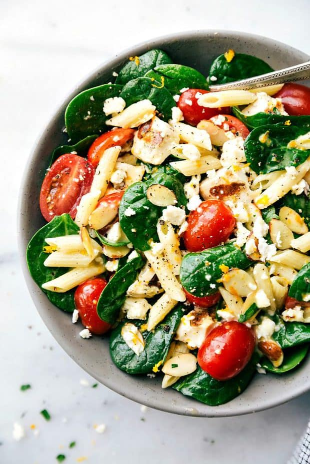 Healthy Chicken Pasta Salad is a spinach salad with penne pasta, grilled chicken, cherry tomatoes, toasted slivered almonds, and a fresh citrus vinaigrette.