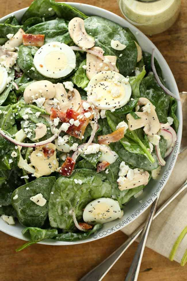 This Classic Spinach Salad recipe is topped with bacon, red onion, fresh mushrooms & boiled eggs. An easy homemade poppy seed dressing this is the perfect complement. This makes a delicious side or isgreat with grilled chicken for a complete meal.