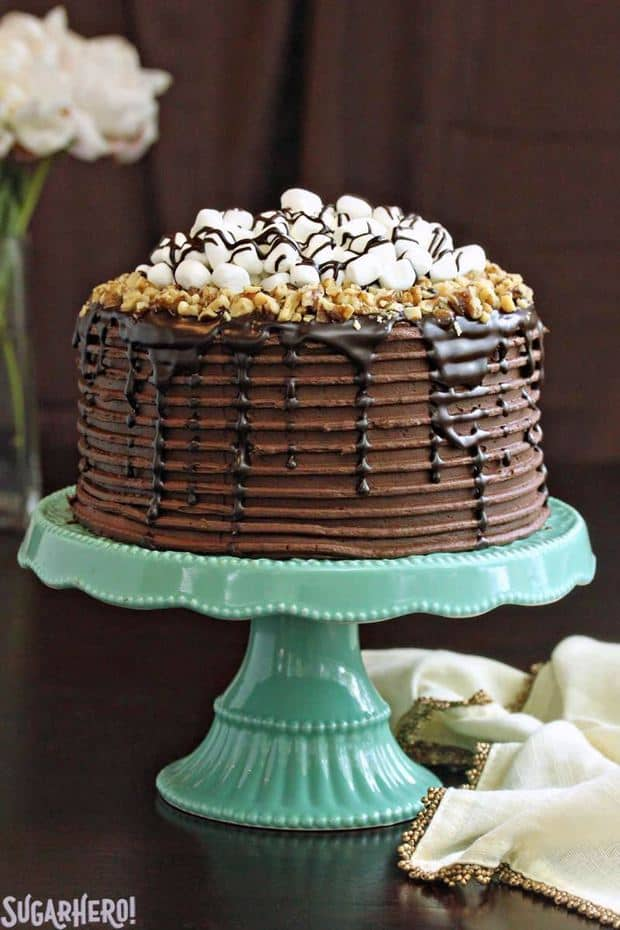 This Rocky Road Layer Cake is chocolate overload, in the best way possible! Moist chocolate cake is layered with a rich filling of marshmallows, nuts, and chocolate ganache. A glorious collection of marshmallows, nuts, ganache, and chocolate buttercream completes this indulgent dessert.