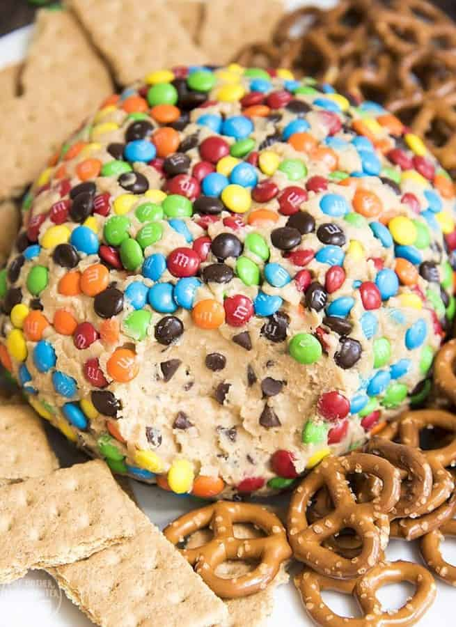Monster Cookie Dough Dip Cheeseball is a delicious peanut butter dessert dip that tastes like monster peanut butter cookies and peanut butter cookie dough. Its perfect served with pretzels, graham crackers, and other cookies!