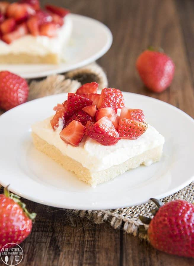 Thick and soft sugar cookie bars topped with whipped cream and strawberries for a delicious and easy treat like a strawberry shortcake in sugar cookie bar form!