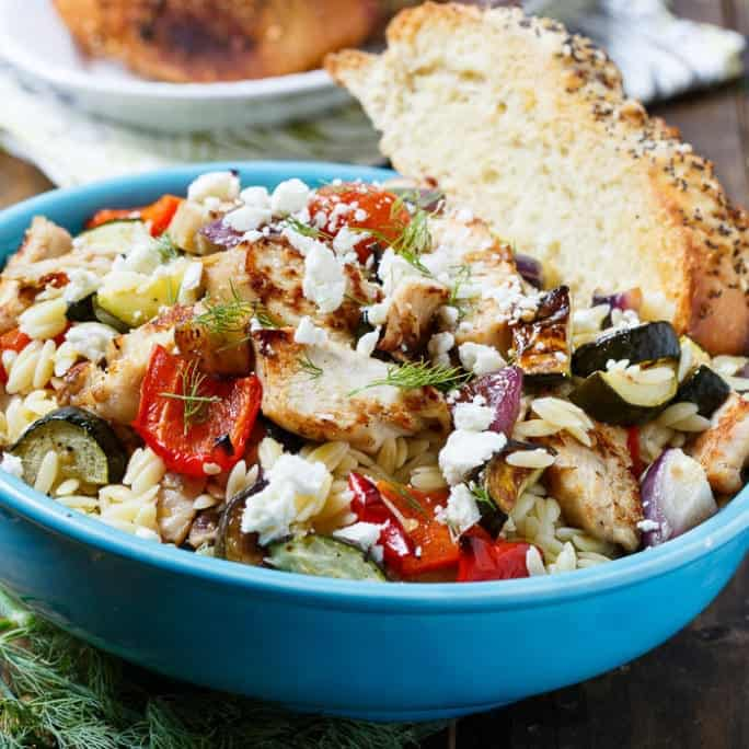 Orzo Pasta Salad with Grilled Chicken and Roasted Vegetables is a one bowl meal that's full of flavor. It's loaded with zucchini, red onion, red bell pepper, and cherry tomatoes, plus a little crumbled feta cheese and fresh dill. Everyone in my family loves pasta salad so much that I often transform it from a side dish into a main dish by adding a protein.