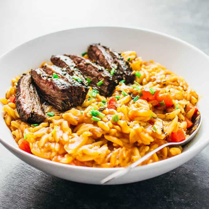 Enjoy marinated skirt steak served over a bed of creamy tomato orzo pasta simmered with Italian spices.
