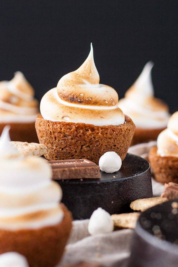 No campfire needed for this S'mores Cookie Cups! Graham cracker cookie cups filled with a hershey's milk chocolate ganache, topped with toasted homemade marshmallow fluff.