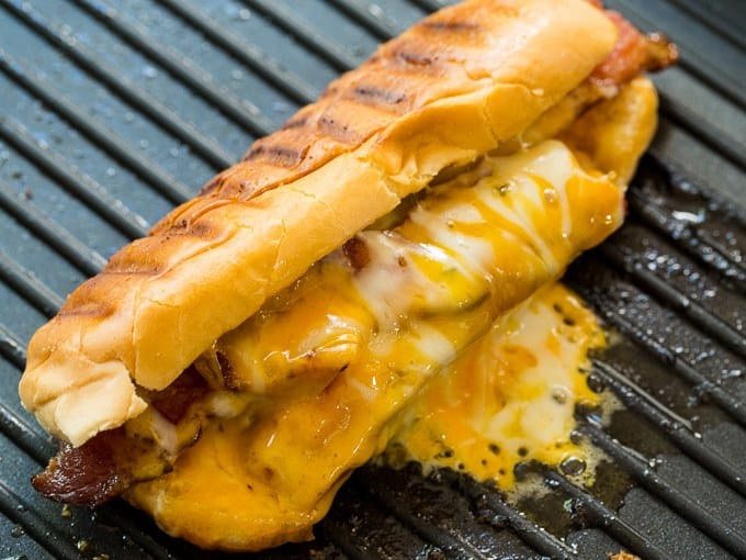 Grilled Cheese Hot Dogs are a super fun and tasty combination of 2 classics- Grilled Cheese and Hot Dogs. A buttery, crispy hot dog bun encases a grilled hot dog with lots of melty cheese and crispy bacon. Lunch doesn't get any better than this!